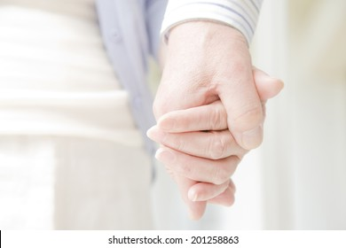 The hands of an elderly couple holding each other's hand