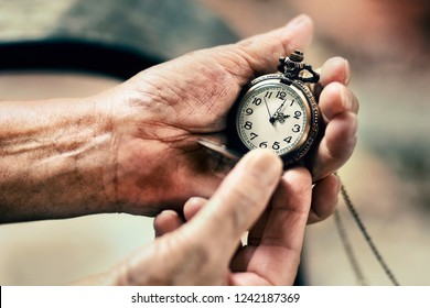 Hands of elderly holding pocket watch in retro vintage color tone.Concept of lonely old senior person waiting for something or depressed elderly.