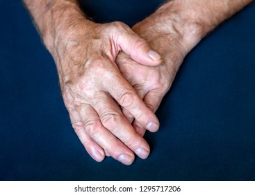 Hands of an elderly man folded together in close-up background