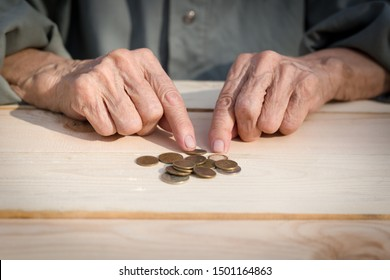 Hands of an elderly man holding coins. The concept of lack of money, the poor, the small pension of old people. Image.