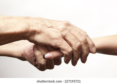 Hands of an elderly man holding the hand of a younger woman