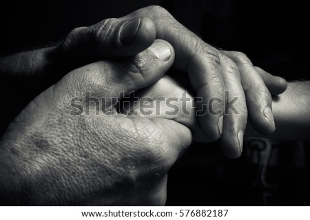 Hands of an elderly man holding the hand of a younger man. Lots of texture and character in the old man hands. black and white