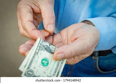 Hands of an elderly man with one us dollar and one cent, the elderly man counts his money. The concept of poverty, small pension, lack of savings.