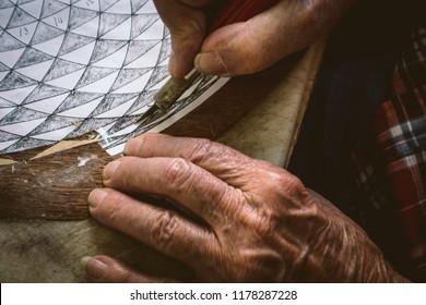 Hands of elderly man working the art of intarsia