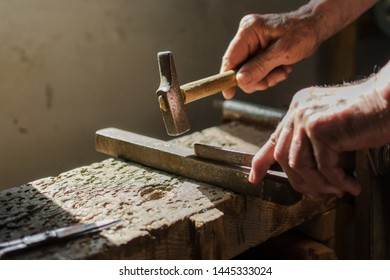 Hands of an elderly man working on the iron with the hammer. Lifestyle concept, worker.