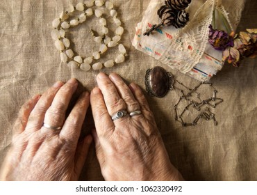 Hands of an elderly person.image of an older lady.Old letters , beads, necklace  and  withered flowers  on the table.   Top view.