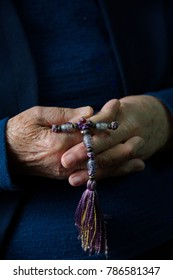 Hands of an elderly woman holding a cloth cross she has made