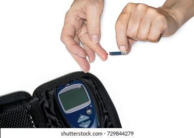 Hands of an elderly woman on white isolated background measure the level of glucose in blood. Applying a drop of blood on a test strip for measuring blood sugar.