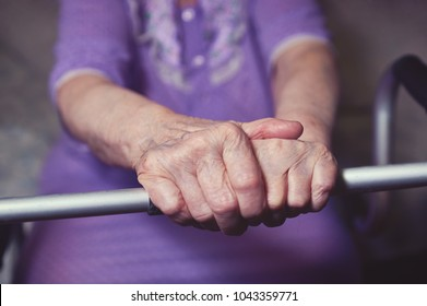 Hands of an elderly woman rests on on a walker. medical and healthcare concept.