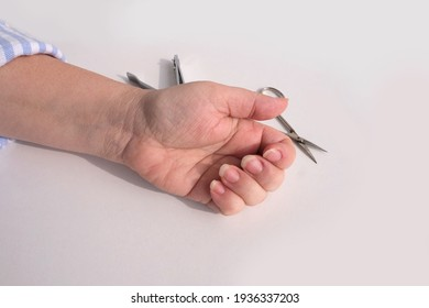hands of an elderly woman in wrinkles close-up, clippers, scissors, cutting nails, care, manicure at home, concept of beauty and spa procedures