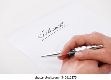 Hands of elderly woman writing ot paper testament