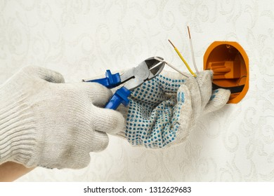 hands of electrician clear the insulation of electrical wires