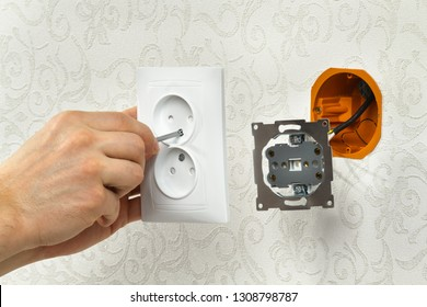 hands of an electrician connect the power outlet