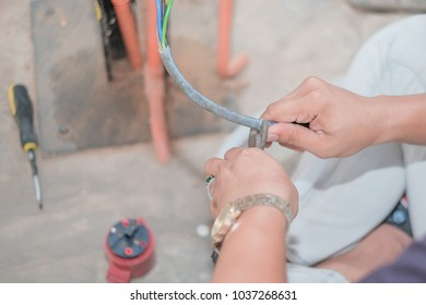 Hands of electrician cutting wires with clippers in wood work workshop.