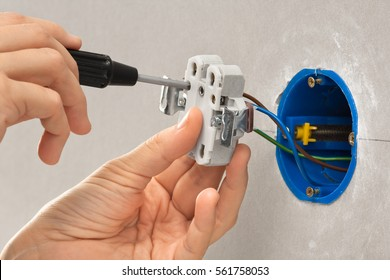 hands of electrician installing electrical socket with screwdriver in the wall