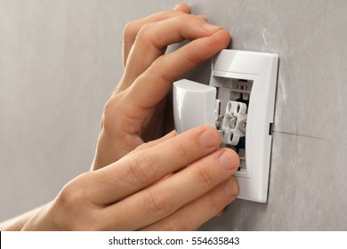 hands of electrician installing light switch on the wall