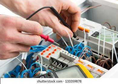 Hands of an electrician with multimeter probe at an electrical switchgear cabinet