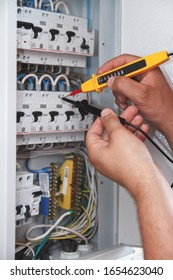 Hands of electrician with multimeter probe at an electrical switchgear cabinet examining fuse box