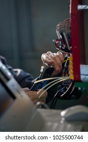 Hands of electrician with stripper installing energy system on machinery industry