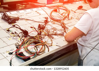 Hands of employees who check the quality of the wiring for cars at a modern plant on a special stand at the production shop