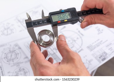 Hands of an engineer measures a metal part with a digital vernier caliper against the background of technical drawings. Quality control of parts machined on a lathe.