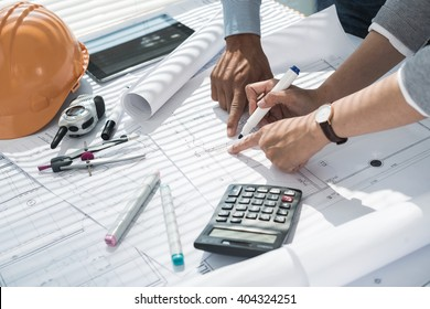 Hands of engineers making corrections in blueprint