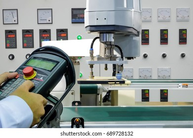 Hands of the engineers are using wireless remote control robot to handle smartphone case flow via a conveyor belt on smart factory, industry 4.0 concept
