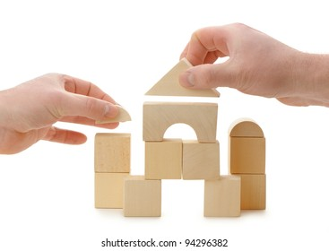 The hands establishes a toy roof on wooden cubes. Isolated on white