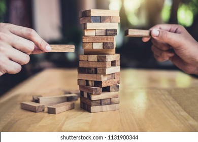 Hands of executive cooperation placing wood block on the tower, Collaborative management, Young intelligent businessman playing the wood game, Alternative risk concept, plan and strategy in business.