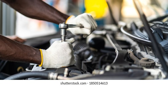 Hands Expertise car mechanic in auto repair service. Car maintenance and auto service garage concept.