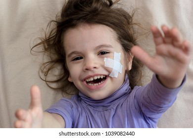 Hands and face with adhesive plaster of young kid girl.