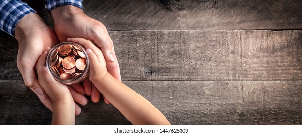 Hands Of Father Giving Jar Of Coins To Child On Wooden Table Background - Inheritance / Parent Providing For Children Concept - Shutterstock ID 1447625309