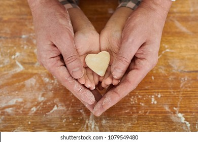 Hands of father and his little daughter holding unprepared heart-shaped cookie together, wooden table covered with flour on background