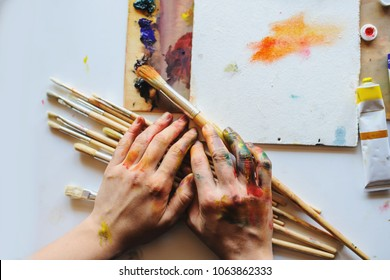 Hands of female artist on the messy dirty palette with different paints and paintbrush in art studio shot from top point. White background