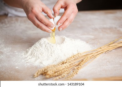 Hands of a female bakery chef breaking an egg into a heap of measured flour while making bread with a bunch of wheat alongside