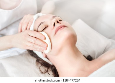 Hands of female beautician cleanses the skin. Facial skincare. Beautiful caucasian woman on a cosmetology procedure. Visit to the beauty salon