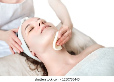 Hands of female beautician cleanses the skin. Sponge. Facial skincare. Beautiful caucasian woman on a cosmetology procedure. Visit to the beauty salon