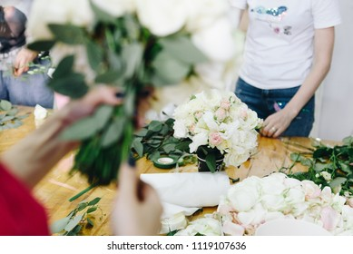 Hands of  female caucasian florist as she is working on a bride's wedding bouquet, another florist in the background