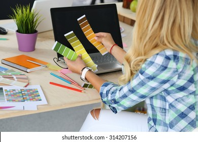 Hands of female designer in office working with colour samples. Woman at workplace choosing colourful paper charts. Creative people or advertising business concept