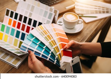 Hands of female designer in office working with colour samples. Woman at workplace choosing colourful paper charts. Close-up.