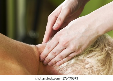 Hands of female massage therapist kneading a mid-aged blond woman's neck