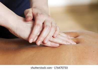 Hands of female massage therapist treating a woman's back