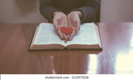 Hands female prayer to Load with broken heart in hands on the bible,Concept Pray for liberation,sin,no freedom.