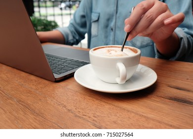 hands of female  stirring tablespoon a cup of coffee and using tablet, tapping screen - technology, work, break concept