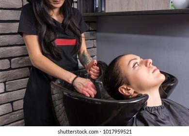 Hands of female stylist washing hair of beautiful woman in washing sink in beauty salon