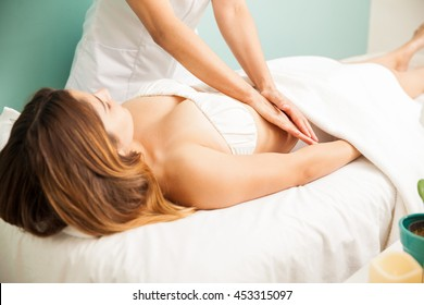 Hands of a female therapist giving a belly massage to one of her clients at a health clinic and spa