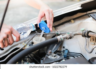 Hands of filling fresh water into the canister of the car windscreen wiper system.