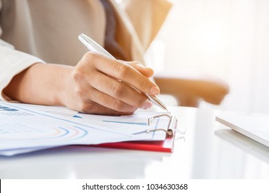 Hands of financial manager taking notes when working on report, Women working in office interior.