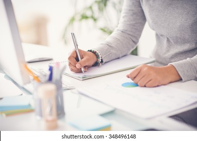 Hands of financial manager taking notes when working on report