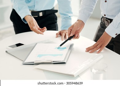 Hands of financial managers analyzing business document
